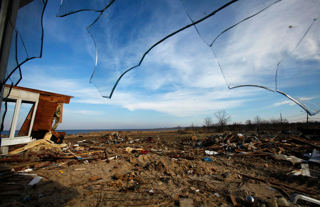 Description of . The debris of a home damaged by Superstorm Sandy is seen on a yard, through broken glass, one month after the disaster at the zone of Union Beach, New Jersey, November 29, 2012. REUTERS/Eduardo Munoz