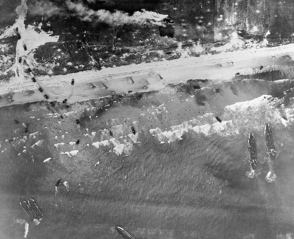 Description of . Men and assault vehicles storm the Normandy Beach of France, as allied landing craft arrive at their destination on D-Day, June 6, 1944. Note men coming ashore in surf and vehicles starting inland. (AP Photo)