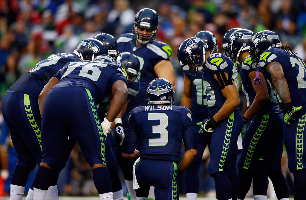 . Quarterback Russell Wilson #3 of the Seattle Seahawks kneels as the team huddles in the first half against the San Francisco 49ers during the 2014 NFC Championship at CenturyLink Field on January 19, 2014 in Seattle, Washington.  (Photo by Jonathan Ferrey/Getty Images)