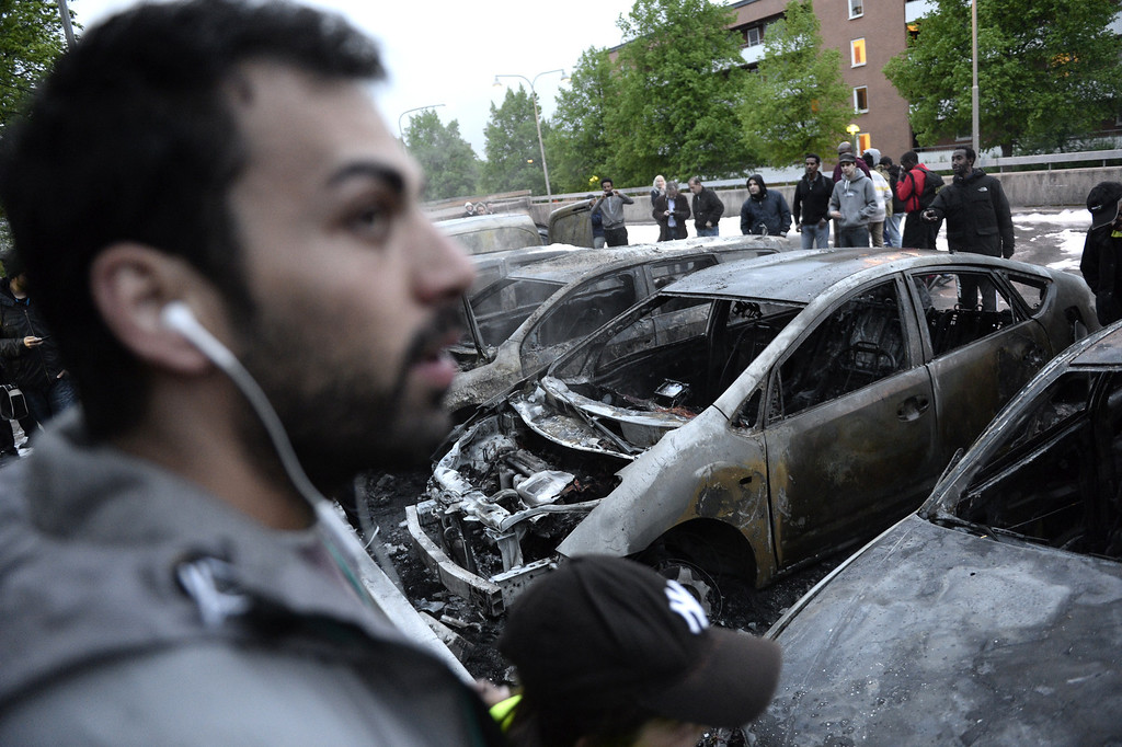 Description of . People look at the scene where cars stand gutted by fire in the Stockholm suburb of Rinkeby after youths rioted in several different suburbs around Stockholm, Sweden for a fourth consecutive night on May 23, 2013. In the suburb of Husby, where the riots began on Sunday in response to the fatal police shooting of a 69-year-old machete-wielding man, 80 percent of residents are immigrants and the unrest has highlighted Sweden's failure to integrate swathes of its immigrant population, but in this small, consensus-driven country, there was little agreement on how to solve the problem.  JONATHAN NACKSTRAND/AFP/Getty Images