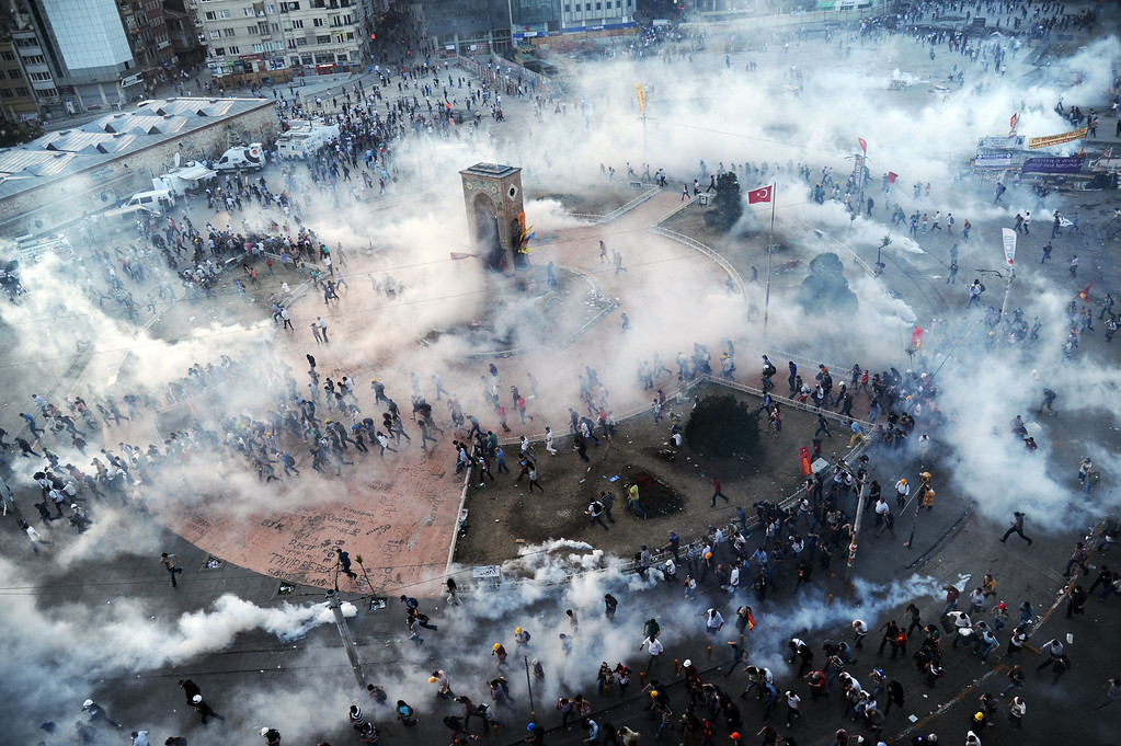 Description of . People run away as Turkish riot policemen fire tear gas on Taksim square on June 11, 2013. Turkish police fired massive volleys of tear gas and jets of water to disperse thousands of anti-government demonstrators in Istanbul's Taksim Square on June 11, after earlier apparently retreating.  BULENT KILIC/AFP/Getty Images