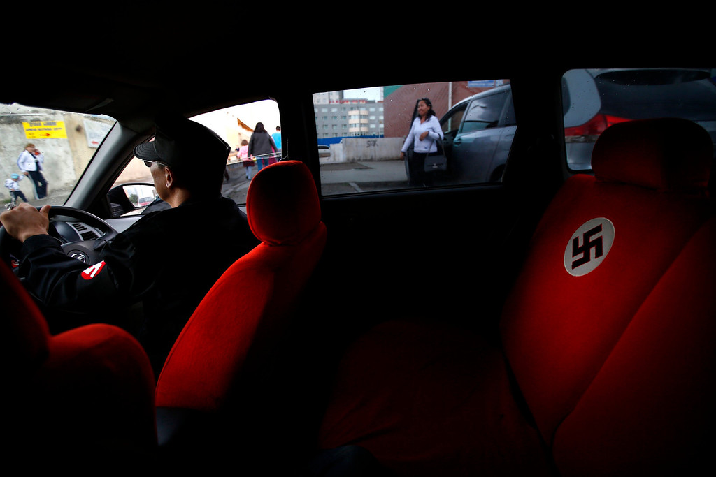 Description of . A swastika is seen on the seat of a car belonging to Ariunbold, leader of the Mongolian neo-Nazi group Tsagaan Khass, as he drives along a busy street in Ulan Bator June 22, 2013. The group has rebranded itself as an environmentalist organisation fighting pollution by foreign-owned mines, seeking legitimacy as it sends Swastika-wearing members to check mining permits. Over the past years, ultra-nationalist groups have expanded in the country and among those garnering attention is Tsagaan Khass, which has recently shifted its focus from activities such as attacks on women it accuses of consorting with foreign men to environmental issues, with the stated goal of protecting Mongolia from foreign mining interests. This ultra-nationalist group was founded in the 1990s and currently has 100-plus members. Picture taken June 22, 2013. REUTERS/Carlos Barria