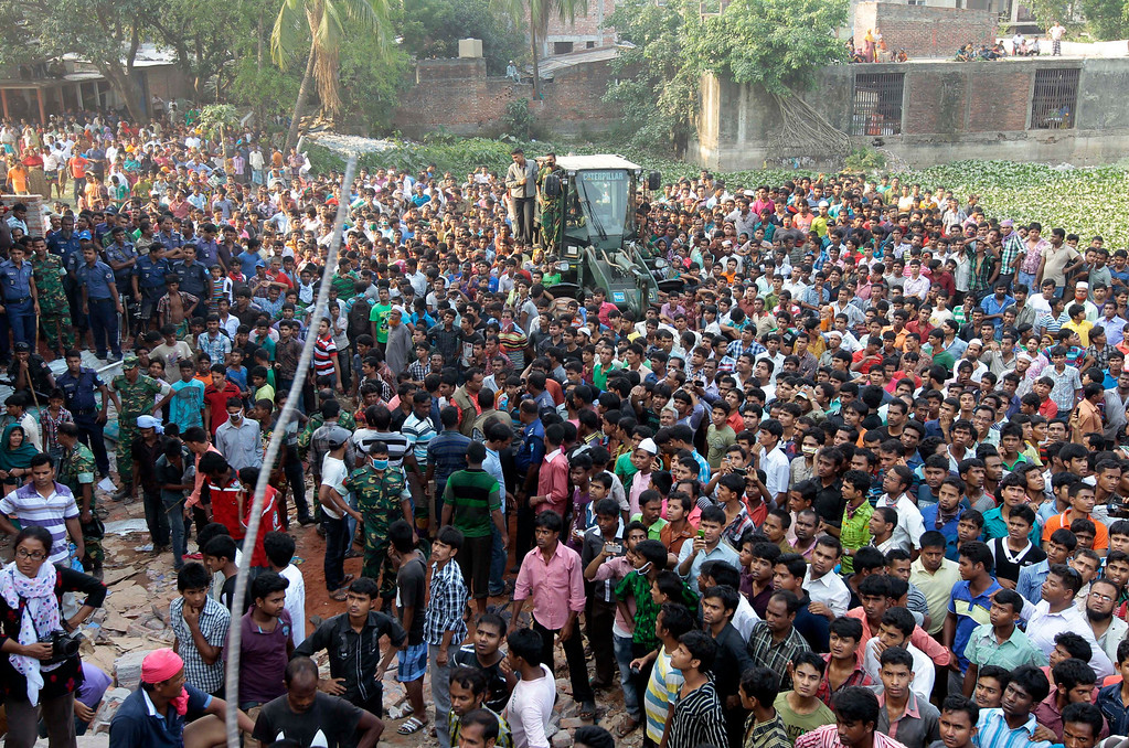 Description of . A crowd gathers to watch rescue work at the site of a building that collapsed in Savar, near Dhaka, Bangladesh, Wednesday, April 24, 2013. (AP Photo/A.M.Ahad)