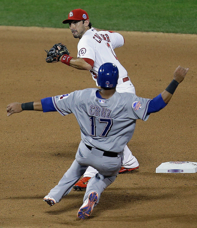 Description of . American League\'s Nelson Cruz, of the Texas Rangers, is out at second as National Leagueís Matt Carpenter, of the St. Louis Cardinals, turns a double play on a ball hit by Edwin Encarnacion during the seventh inning of the MLB All-Star baseball game, on Tuesday, July 16, 2013, in New York. (AP Photo/Julio Cortez)