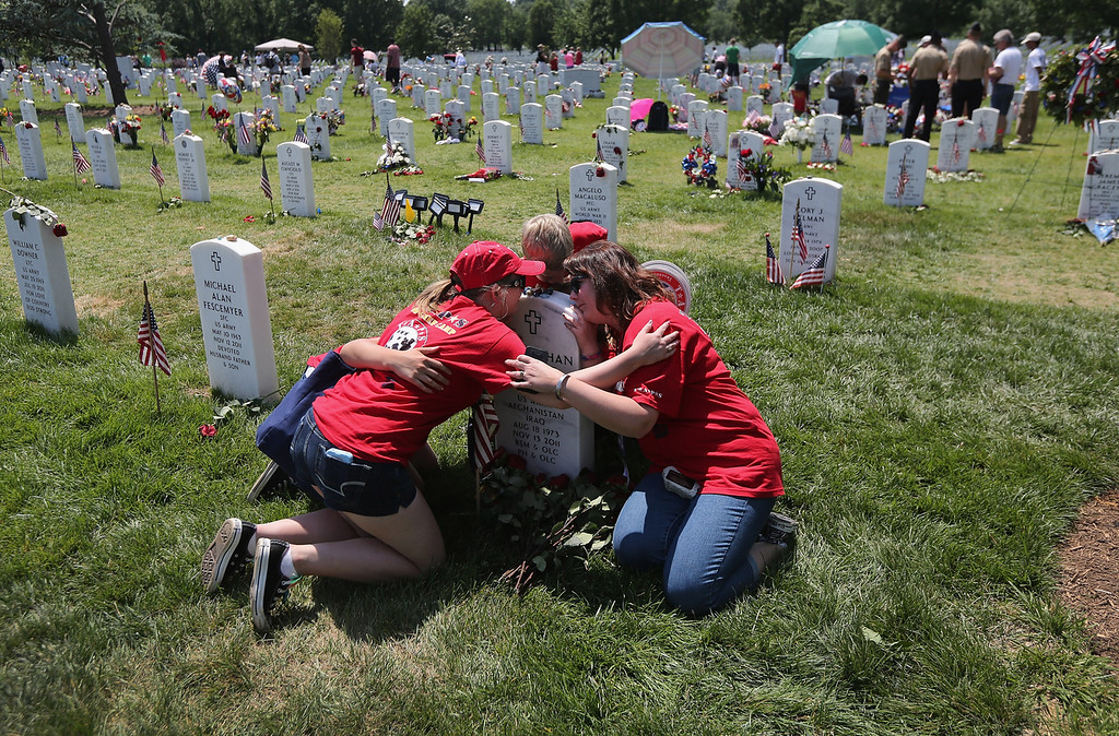 Description of . Leanne McCain (R), and her children of North Pole, Alaska embrace over her slain husband's grave at the National Cemetery on May 28, 2012 in Arlington, Virginia. Her husband and father of four, Army SFC Johnathan McCain, was killed by a roadside bomb in Afghanistan in November 2011. She brought her children this year to take part in a TAPS