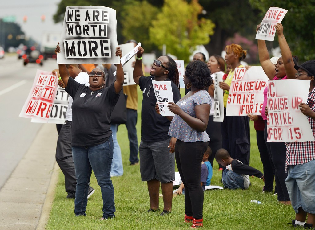 Description of . Protesters line a portion of the 4600 block of Capitol Blvd. in Raleigh, North Carolina, at a rally calling for a $15-an-hour wage for fast-food workers, Thursday, August 29, 2013. The rally is one of several nationally. (Scott Sharpe/Raleigh News & Observer/MCT)