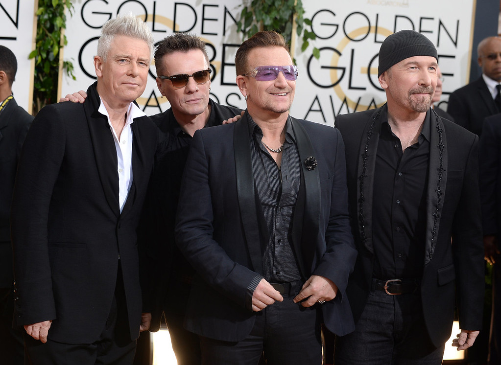 Description of . Members of the Irish rock band U2, from left, Adam Clayton, Larry Mullen, Jr., Bono, and The Edge arrive at the 71st annual Golden Globe Awards at the Beverly Hilton Hotel on Sunday, Jan. 12, 2014, in Beverly Hills, Calif. (Photo by Jordan Strauss/Invision/AP)