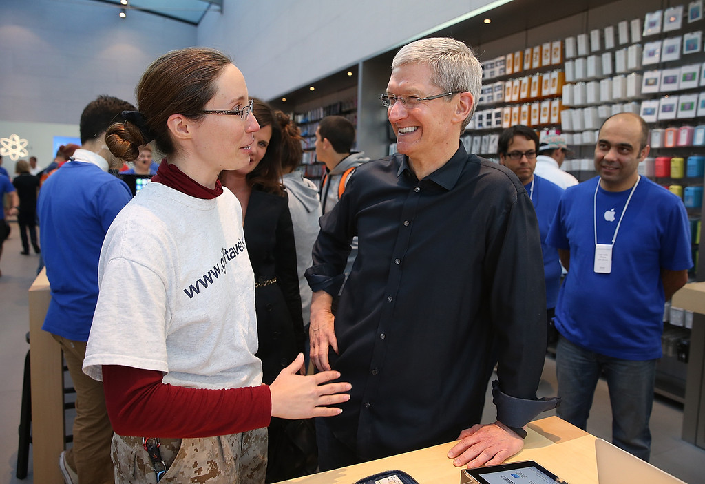 Description of . Apple CEO Tim Cook (R) talks with Dorothy Arndt (L) who just purchased the new iPhone on September 20, 2013 in Palo Alto, California.  (Photo by Justin Sullivan/Getty Images)