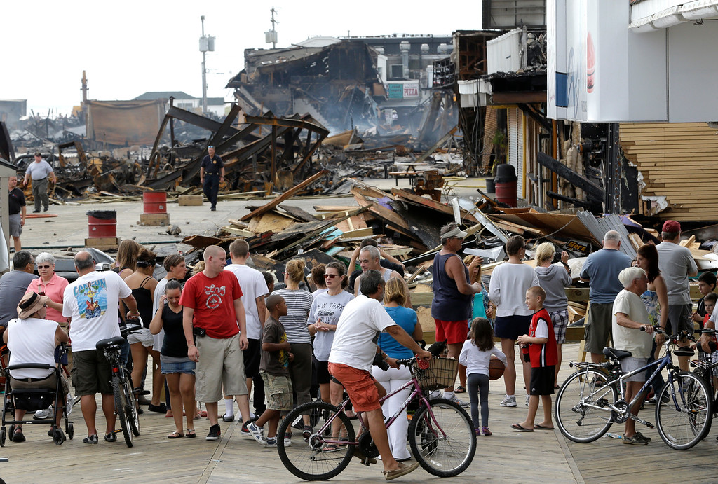 Description of . People gather at a barricade to catch a glimpse of the destruction left behind a day after a massive fire burned a large portion of the Seaside Park boardwalk, Friday, Sept. 13, 2013, in Seaside Park, N.J. (AP Photo/Julio Cortez)