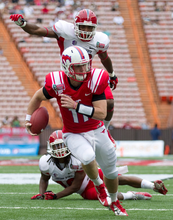 Description of . Fresno State safety Phillip Thomas, bottom, and linebacker Tristan Okpalaugo, top, watch as SMU quarterback Garrett Gilbert (11) breaks a tackle and runs in for a touchdown in the second quarter of the Hawaii Bowl NCAA college football game Monday, Dec. 24, 2012, in Honolulu. (AP Photo/Eugene Tanner)