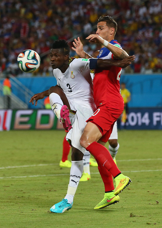 Description of . Asamoah Gyan of Ghana holds off a challenge by Geoff Cameron of the United States during the 2014 FIFA World Cup Brazil Group G match between Ghana and the United States at Estadio das Dunas on June 16, 2014 in Natal, Brazil.  (Photo by Kevin C. Cox/Getty Images)