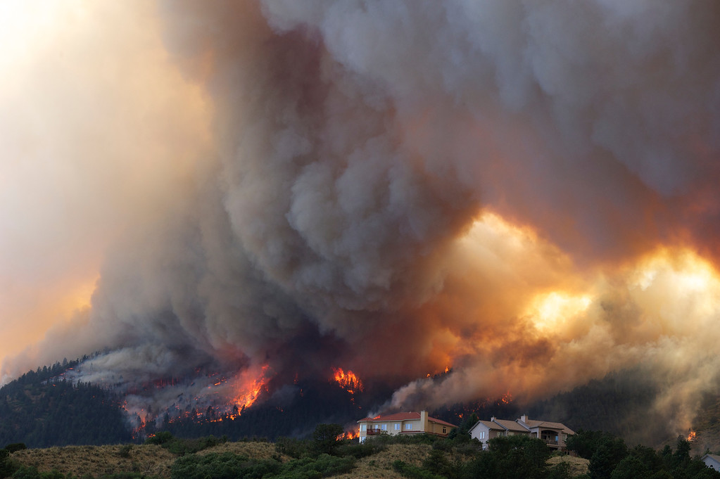 Description of . In this June 26, 2012 file photo, fire from the Waldo Canyon wildfire burns as it moved into subdivisions and destroyed homes in Colorado Springs, Colo. (AP Photo/Gaylon Wampler, File)