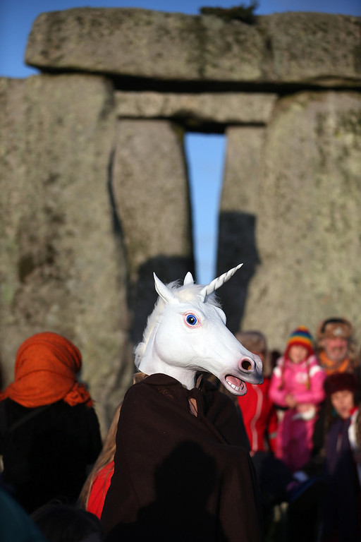 Description of . A woman dressed as a unicorn watches the sun rise, as druids, pagans and revellers take part in a winter solstice ceremony at Stonehenge on December 21, 2012 in Wiltshire, England. Predictions that the world will end today as it marks the end of a 5,125-year-long cycle in the ancient Maya calendar, encouraged a larger than normal crowd to gather at the famous historic stone circle to celebrate the sunrise closest to the Winter Solstice, the shortest day of the year.  (Photo by Matt Cardy/Getty Images)