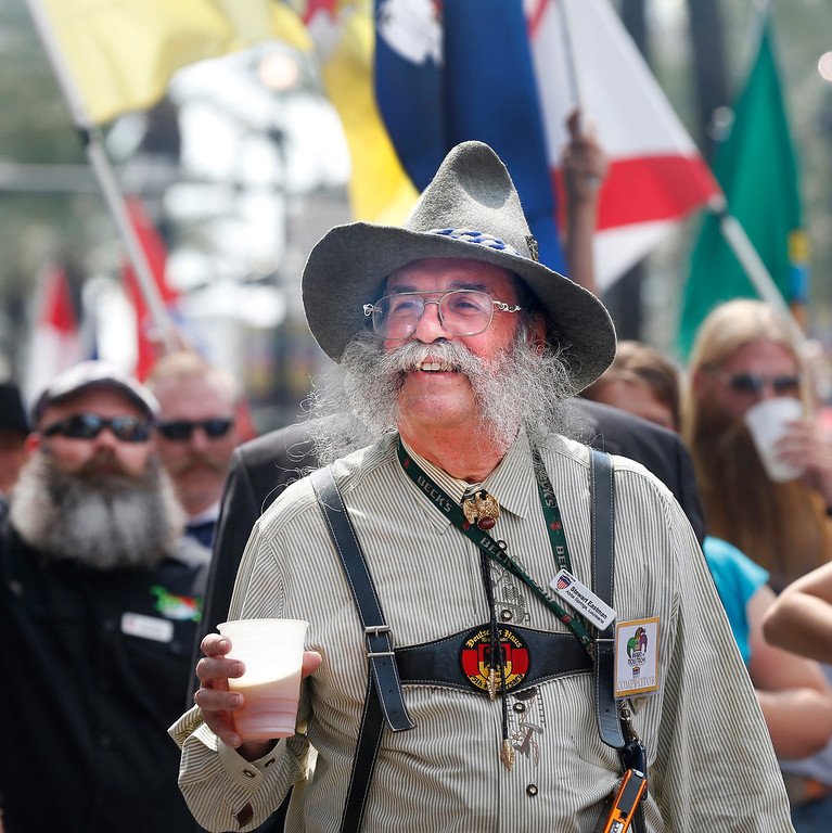 Description of . Stewart Eastman of Abita Springs, Louisiana enjoys a beer while parading through the French Quarter to kick off the fourth annual Just For Men National Beard and Moustache Championships Saturday, Sept. 7, 2013 in New Orleans. Contestants competed in 18 different categories including Dali, full beard natural and sideburns. (AP Photo/Susan Poag)