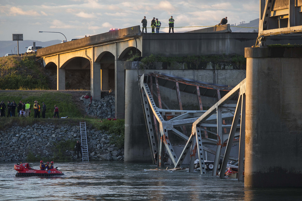 Description of . A portion of the Interstate 5 bridge is submerged after it collapsed into the Skagit River dumping vehicles and people into the water as rescuers watch from the collapsed section of Interstate 5 and hovercraft search for survivors below in Mount Vernon, Wash., Thursday, May 23, 2013.  (AP Photo/The Seattle Times, Rick Lund)