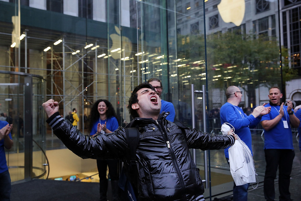 Description of . The first customer in line, Rami Shamis, celebrates his purchase of the new iPad Air at the Apple Store on November 1, 2013 in New York City.   (Photo by Spencer Platt/Getty Images)