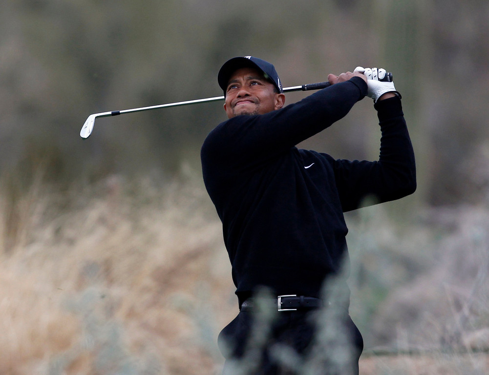 Description of . Tiger Woods of the U.S. hits off the 12th tee against Charles Howell III of the U.S. during the weather delayed first round of the WGC-Accenture Match Play Championship golf tournament in Marana, Arizona February 21, 2013. REUTERS/Matt Sullivan