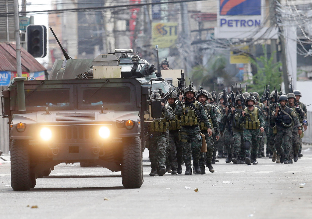 Description of . Fresh troops arrive to reinforce other government troopers as they continue their assault at Muslim rebels Thursday, Sept. 12, 2013 in Zamboanga city in southern Philippines.  (AP Photo/Bullit Marquez)