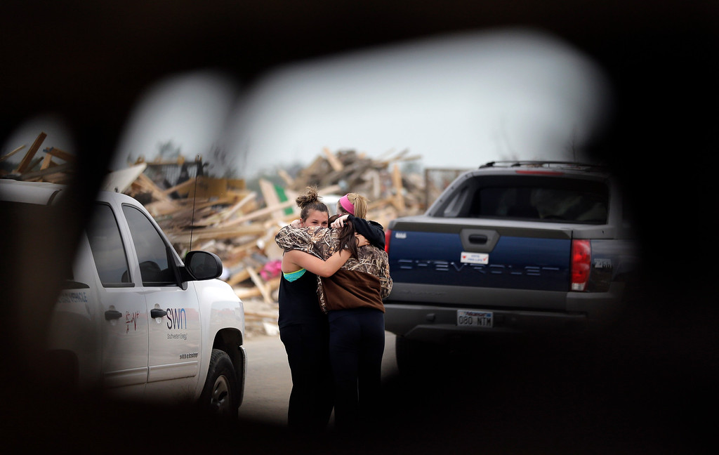 Description of . Friends, seen through debris, comfort each other at the site of a a home destroyed by Sunday's tornado, Tuesday, April 29, 2014, in Vilonia, Ark.  (AP Photo/Eric Gay)