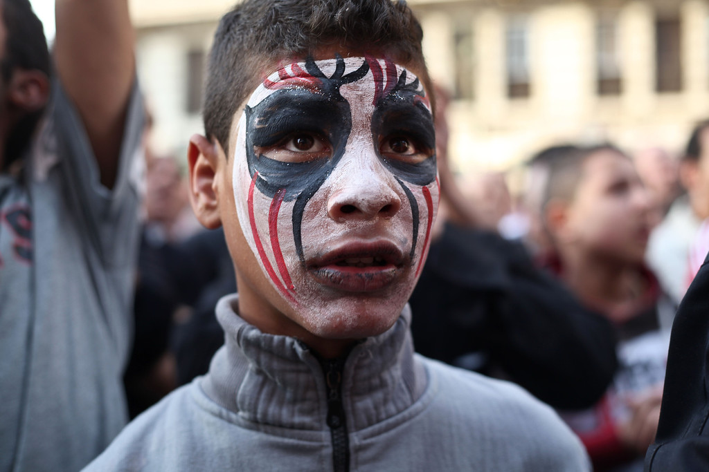 Description of . An Egyptian youth wears face paint at a demonstration outside the country's high court in Cairo, Egypt, Saturday, April 6, 2013. Thousands of activists took to the streets Saturday to mark the fifth anniversary of the founding of a leading opposition group, the April 6 Youth Movement, and to push a long list of demands on Morsi, including the formation of a more inclusive government amid a worsening economy.(AP Photo/Ariana Drehsler)