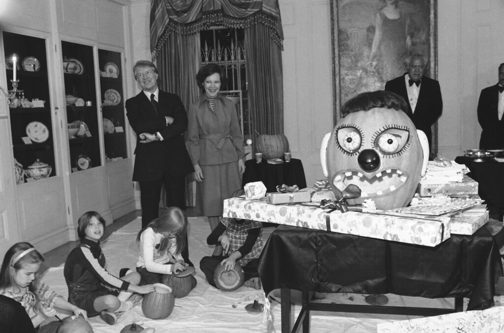 Description of . President Jimmy  Carter and Mrs. Rosalynn Carter stand by as daughter Amy and some of her friends carve pumpkins during Amy's 10th birthday party  Wednesday, Oct. 19, 1977 in the White House in Washington. Amy is seated directly in front of the President. (AP Photo)