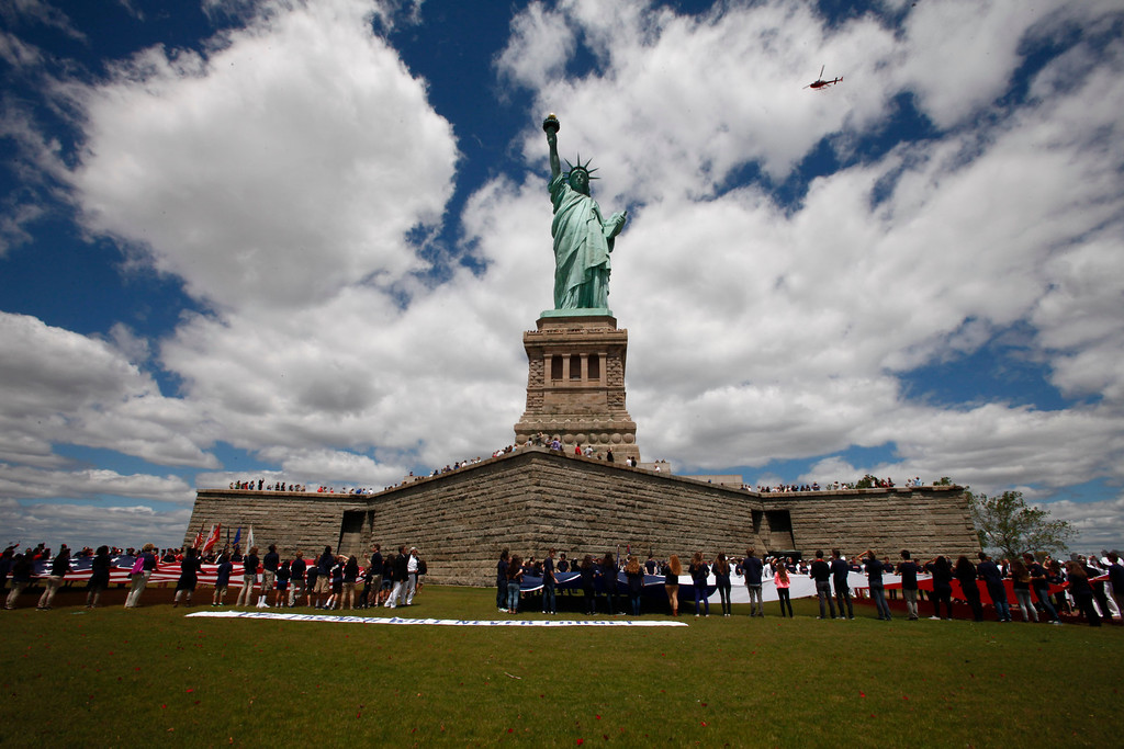 Description of . Three helicopters flies before drops rose petals over the statue of liberty during the Commemorating 70th flies Anniversary of D-Day on June 06, 2014 in New York City. Three helicopters have showered 1 million rose petals on the Statue during a event organized by the organization