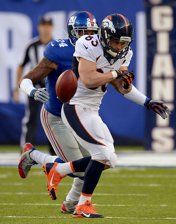 Description of . Denver Broncos wide receiver Wes Welker (83) can't hang on to a pass as he gets hit by New York Giants defensive back Terrell Thomas (24)  during the second quarter September 15, 2013 MetLife Stadium. (Photo by John Leyba/The Denver Post)