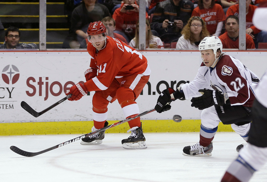 Description of . Detroit Red Wings right wing Daniel Cleary (11) passes the puck in front of Colorado Avalanche defenseman Matt Hunwick (22) during the second period of an NHL hockey game in Detroit, Tuesday, March 5, 2013. (AP Photo/Carlos Osorio)