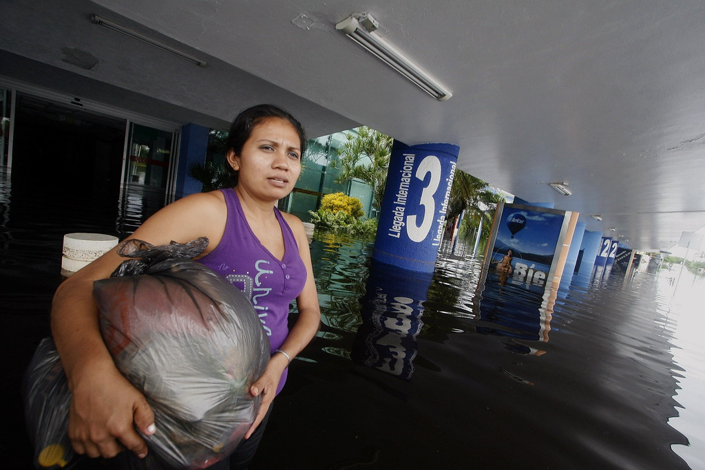 Description of . A woman wades through the water at the airport of Acapulco, flooded by heavy rains that have been hitting the country, in Guerrero state, Mexico, on September 17, 2013. Mexican authorities scrambled Tuesday to launch an air lift to evacuate tens of thousands of tourists stranded amid floods in the resort of Acapulco following a pair of deadly storms. At least 48 people were killed and thousands evacuated from towns on the Pacific and Gulf of Mexico coasts over the weekend as Tropical Storm Manuel and downgraded Hurricane Ingrid set off landslides and floods that damaged bridges, roads and homes.  Pedro PARDO/AFP/Getty Images