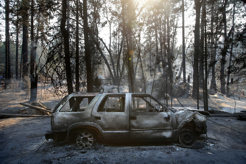 Description of . A burned SUV sits in front of a campground destroyed by the Rim Fire near Yosemite National Park, Calif., on Monday, Aug. 26, 2013. Crews working to contain one of California's largest-ever wildfires gained some ground Monday against the flames threatening San Francisco's water supply, several towns near Yosemite National Park and historic giant sequoias. (AP Photo/Jae C. Hong)