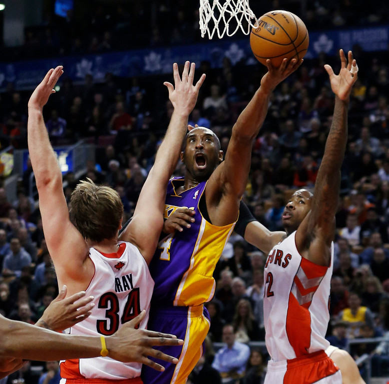 Description of . Los Angeles Lakers' Kobe Bryant (C) goes to the basket against Toronto Raptors' Aaron Gray (L) and Ed Davis during the first half of their NBA basketball game in Toronto, January 20, 2013.     REUTERS/Mark Blinch