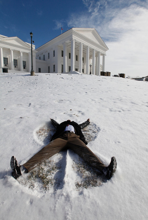 Description of . Del. K. Rob Krupicka, D-Alexandria, makes a snow angel on  the front lawn of the Virginia State Capitol in Richmond, Va., Wednesday, Jan. 29, 2014.   (AP Photo/Richmond Times-Dispatch, Bob Brown).