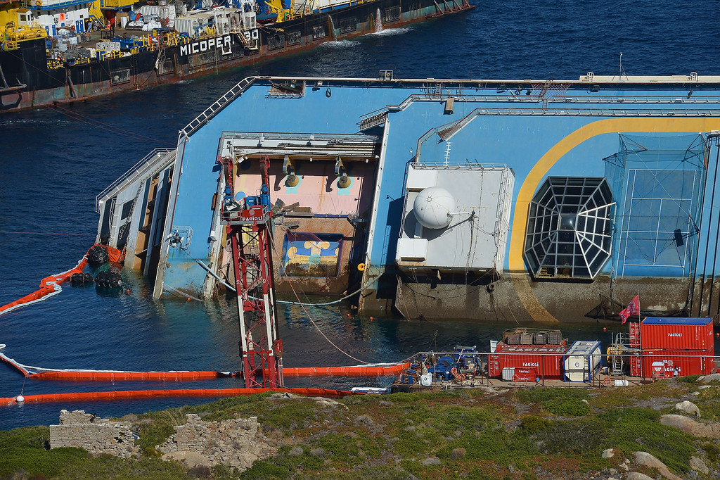 Description of . A pictures shows a part of the wreck of Italy's Costa Concordia cruise ship which begins to emerge from water near the harbor of Giglio Porto on September 16, 2013. Salvage workers will attempt to raise the cruise ship today, in the largest and most expensive maritime salvage operation in history, so-called