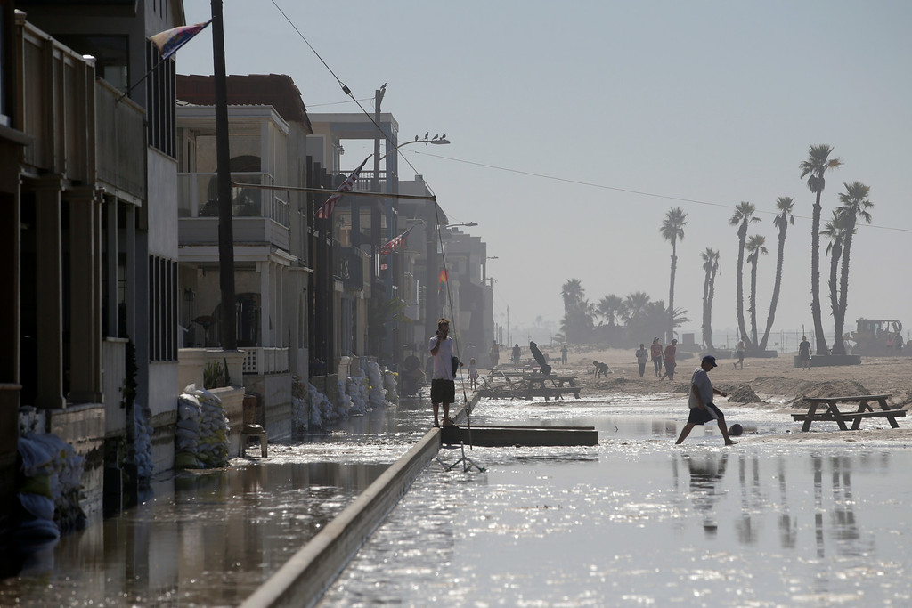 Description of . A man walks through the flooded beachfront properties on Wednesday, Aug. 27, 2014, in Seal Beach, Calif. A low-lying street in the Southern California coastal community of Seal Beach has been inundated by a surge of rising seawater brought on by Hurricane Marie spinning off Mexico's Pacific coast. (AP Photo/Jae C. Hong)