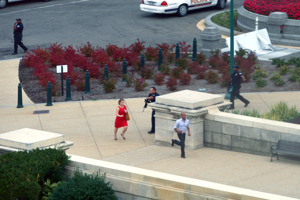 Description of . People run for cover as police converge to the site of a shooting October 3, 2013 on Capitol Hill in Washington, DC. The US Capitol was placed on security lockdown Thursday after shots were fired outside the complex, senators said.