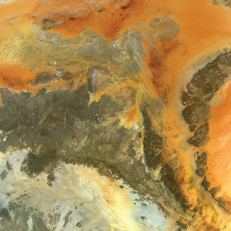 Description of . Three Massifs, Sahara Desert Three large rock massifs appear to be pushing up from beneath red sand dunes in this 2000 Terra image. The Tassili n�Ajjer massif is on the left, the Tadrart Acacus is in the middle, and the Tadrart Amsak is on the right. The image includes the southern part of the border between Algeria and Libya, and different rock types account for varying colors. The Tadrart Acacus massif contains some unique scenery and natural wonders, including colored sand dunes and isolated towers that eroded into bizarre shapes and petrified arches. The dendritic structures of ancient riverbeds are visible in the Acacus-Amsak region. This area is believed to have been wet during the last glacial era, covered by forests and populated by wild animals. Archaeologists have found indications of animal domestication and large numbers of rock paintings and engravings, faint tracks of ancient civilizations. Extremely dry weather conditions today help to preserve their masterpieces.   NASA
