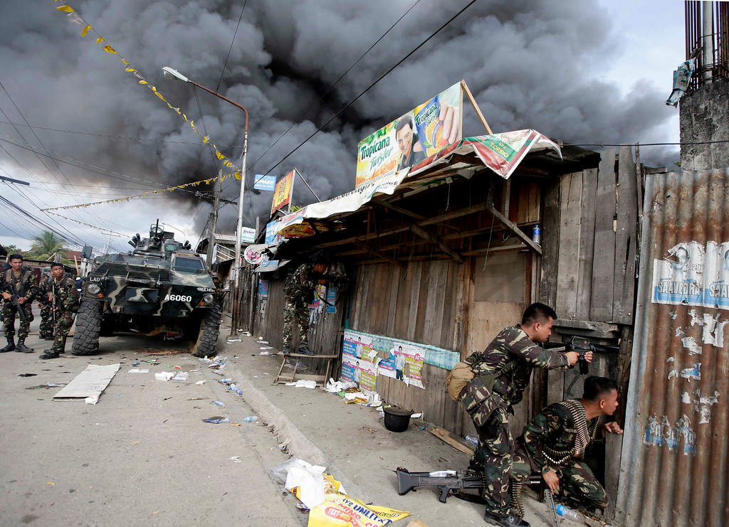 Description of . Government troopers continue their assault on Muslim rebels Thursday, Sept. 12, 2013, in Zamboanga city in the southern Philippines.  (AP Photo/Bullit Marquez)