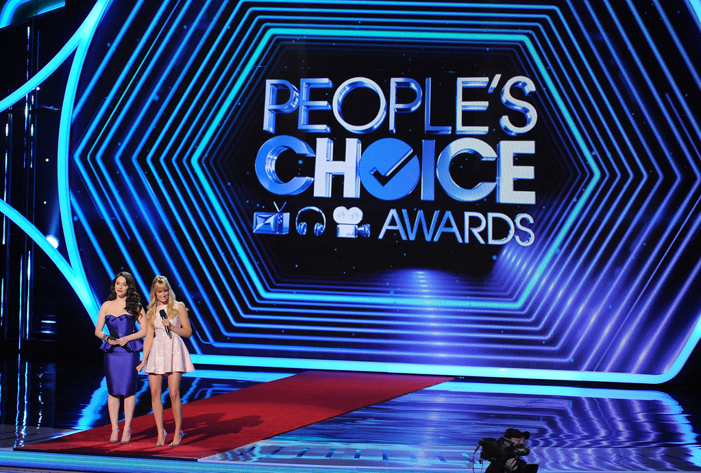 Description of . Hosts Kat Dennings, left, and Beth Behrs speak on stage at the 40th annual People's Choice Awards at the Nokia Theatre L.A. Live on Wednesday, Jan. 8, 2014, in Los Angeles. (Photo by Chris Pizzello/Invision/AP)
