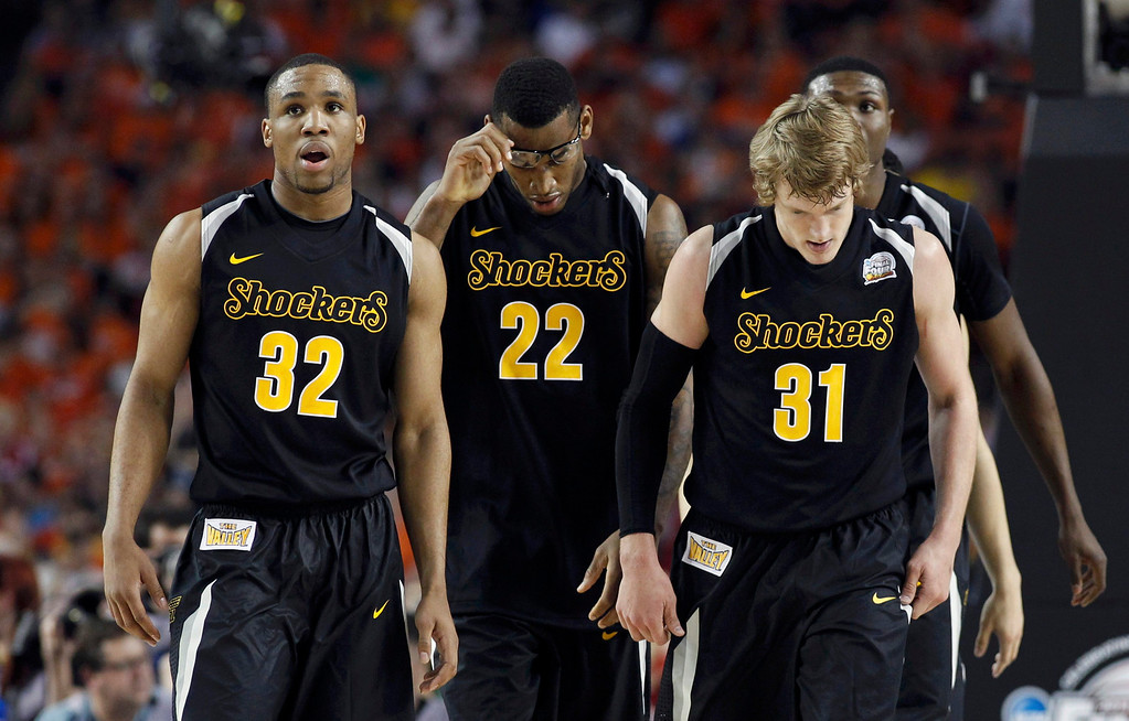 Description of . Wichita State Shockers guard Tekele Cotton (L), forward Carl Hall (C) and guard Ron Baker leave the court for a timeout during the second half of their NCAA men's Final Four basketball game against the Louisville Cardinals in Atlanta, Georgia April 6, 2013. REUTERS/Jeff Haynes