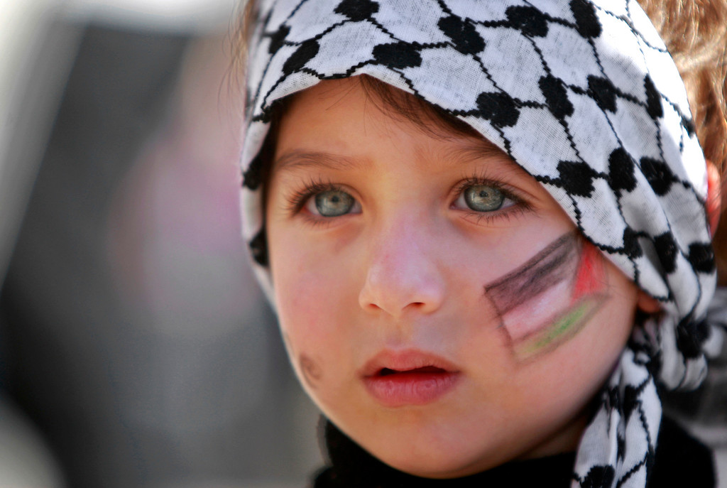 Description of . A girl with the Palestinian flag painted  on her face attends a rally supporting the Palestinian UN bid for observer state status, in the West bank city of Ramallah, Thursday, Nov. 29, 2012. The Palestinians are certain to win U.N. recognition as a state on Thursday but success could exact a high price: delaying an independent state of Palestine because of Israel's vehement opposition. (AP Photo/Majdi Mohammed)