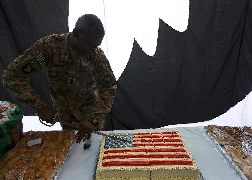 Description of . A U.S. soldier cuts into a cake during Fourth of July celebrations at the Bagram airbase, north of Kabul July 4, 2013. The United States celebrates its Independence Day on July 4. REUTERS/Omar Sobhani