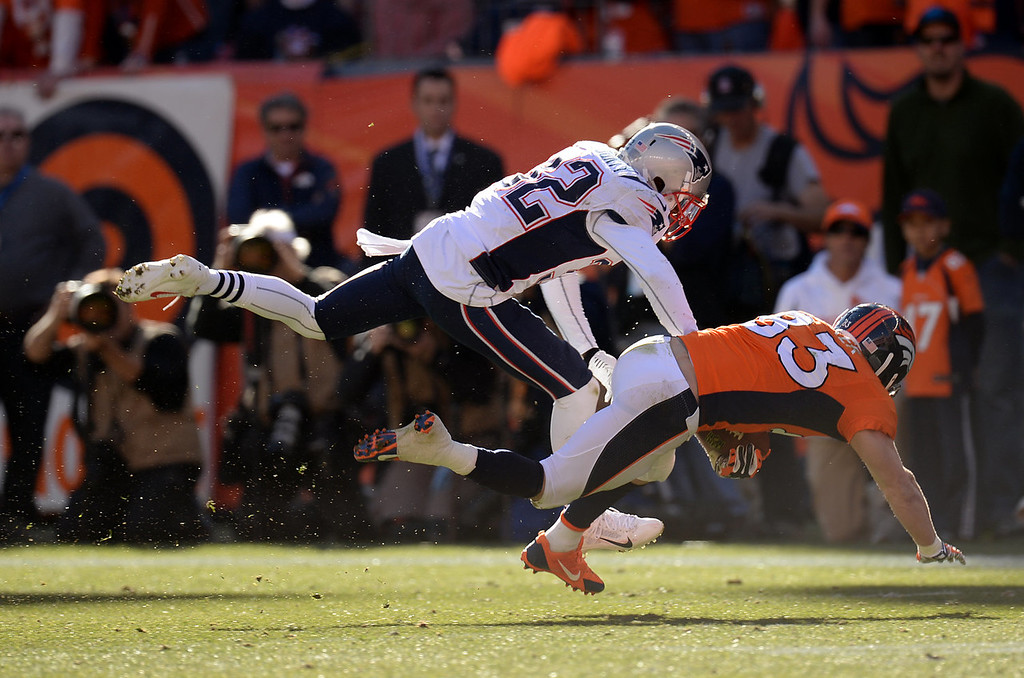 Description of . Denver Broncos wide receiver Wes Welker (83) is tackled by Denver Broncos cornerback Tony Carter (32) in the second quarter. The Denver Broncos take on the New England Patriots in the AFC Championship game at Sports Authority Field at Mile High in Denver on January 19, 2014. (Photo by Hyoung Chang/The Denver Post)