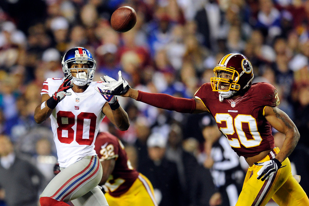 Description of . New York Giants wide receiver Victor Cruz (80) pulls in a pass under pressure from Washington Redskins defensive back Cedric Griffin (20) during the first half of an NFL football game in Landover, Md., Monday, Dec. 3, 2012. (AP Photo/Nick Wass)