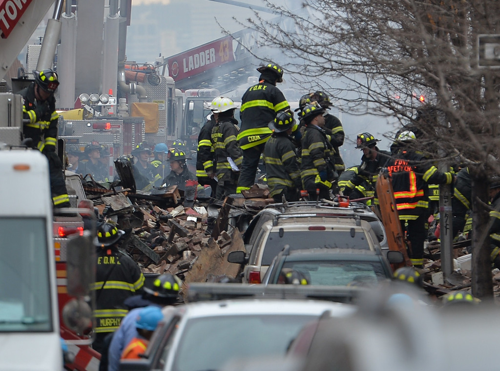 Description of . New York City Fire Department firefighters at the scene of an explosion and building collapse at Park Avenue and East 116th Street March 12, 2014 in the Harlem section of New York.   AFP PHOTO/Stan HONDA/AFP/Getty Images