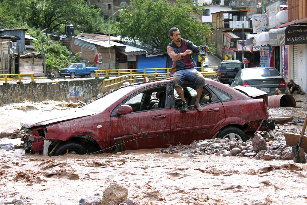 Description of . A man sits atop a car while trying to cross a flooded street in Chilpancingo, state of Guerrero, Mexico, on September 17, 2013. Mexican authorities scrambled Tuesday to launch an air lift to evacuate tens of thousands of tourists stranded amid floods in the resort of Acapulco following a pair of deadly storms. The official death toll rose to 47 after the tropical storms, Ingrid and Manuel, swarmed large swaths of the country during a three-day holiday weekend, sparking landslides and causing rivers to overflow in several states.  EDUARDO GUERRERO/AFP/Getty Images