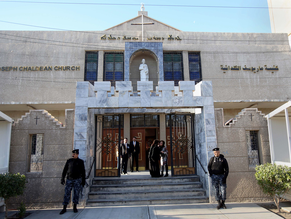 Description of . Iraqi police officers guard the entrance of St. Joseph's Chaldean Church before a Christmas mass in Baghdad, Iraq, Wednesday, Dec. 25, 2013. Militants on Wednesday launched two separate attacks against Christians in Baghdad, officials said. There was no immediate claim of responsibility for the attacks, but Iraq's dwindling Christian community, which is estimated to number about 400,000 to 600,000 people, has often been targeted by al-Qaida and other insurgents who see the Christians as unbelievers.(AP Photo/Karim Kadim)