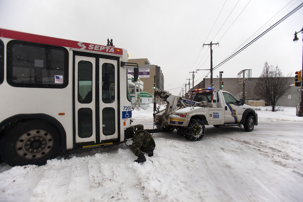 Description of . Police work to tow away a Septa bus that slid off the road on February 13, 2014 in Philadelphia, Pennsylvania. The east coast was hit with a winter snowstorm bringing sleet and snow. (Photo by Jessica Kourkounis/Getty Images)