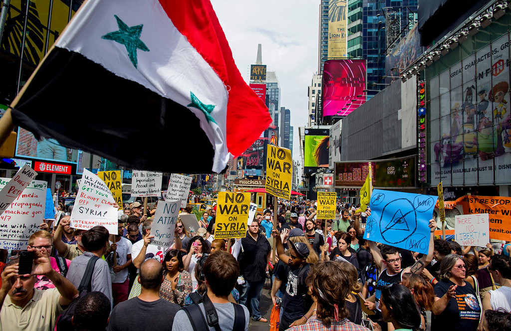 Description of . Opponents of U.S. military action in Syria demonstrate at New York's Times Square on Saturday, Aug. 31, 2013. Protesters around the world took to the streets Saturday to protest for and against a possible U.S.-led attack on Syria as President Barack Obama announced he would seek congressional approval for such a move. (AP Photo/Craig Ruttle)