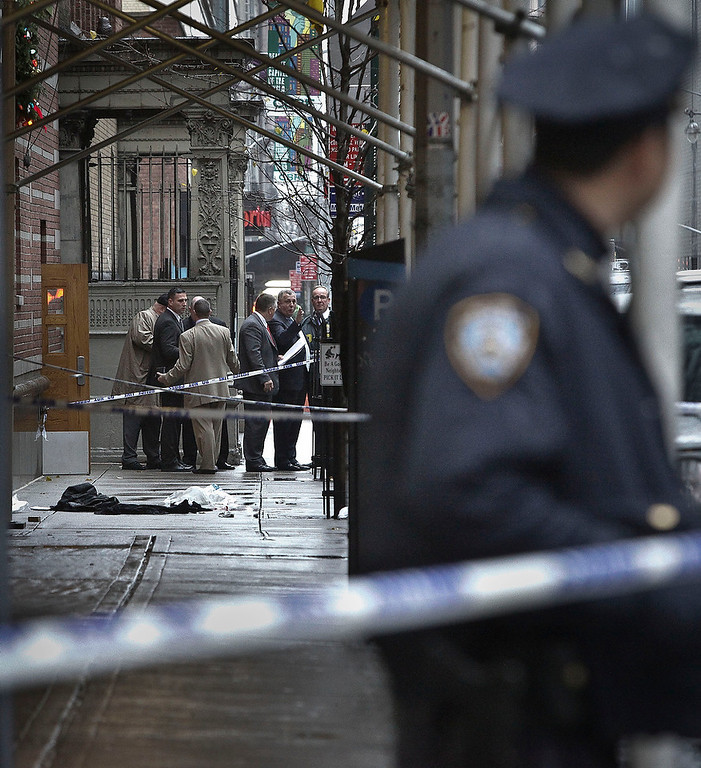 Description of . Police investigate the scene where a man was fatally shot in the back of the head in New York on Monday, Dec. 10, 2012. Authorities said the man was shot outside a school near Columbus Circle in Manhattan, lying mortally wounded in a pool of blood as the suspect escaped with a getaway driver. (AP Photo/Bebeto Matthews)
