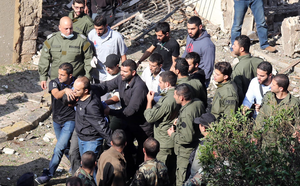 Description of . Hezbollah and Iranian security along with Municipal police detain a suspect in Bir Hassan neighbourhood in the southern Beirut on November 19, 2013.  AFP PHOTO/STR-/AFP/Getty Images